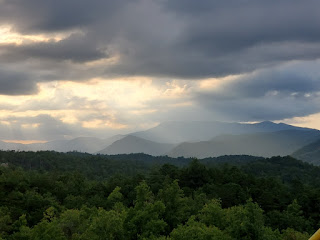 mountain top view of the Great Smokey Mountains, green tree tops in foreground and 'smokey' dark mountains in the background all highlighted by sunlight filtering through the cloudy sky