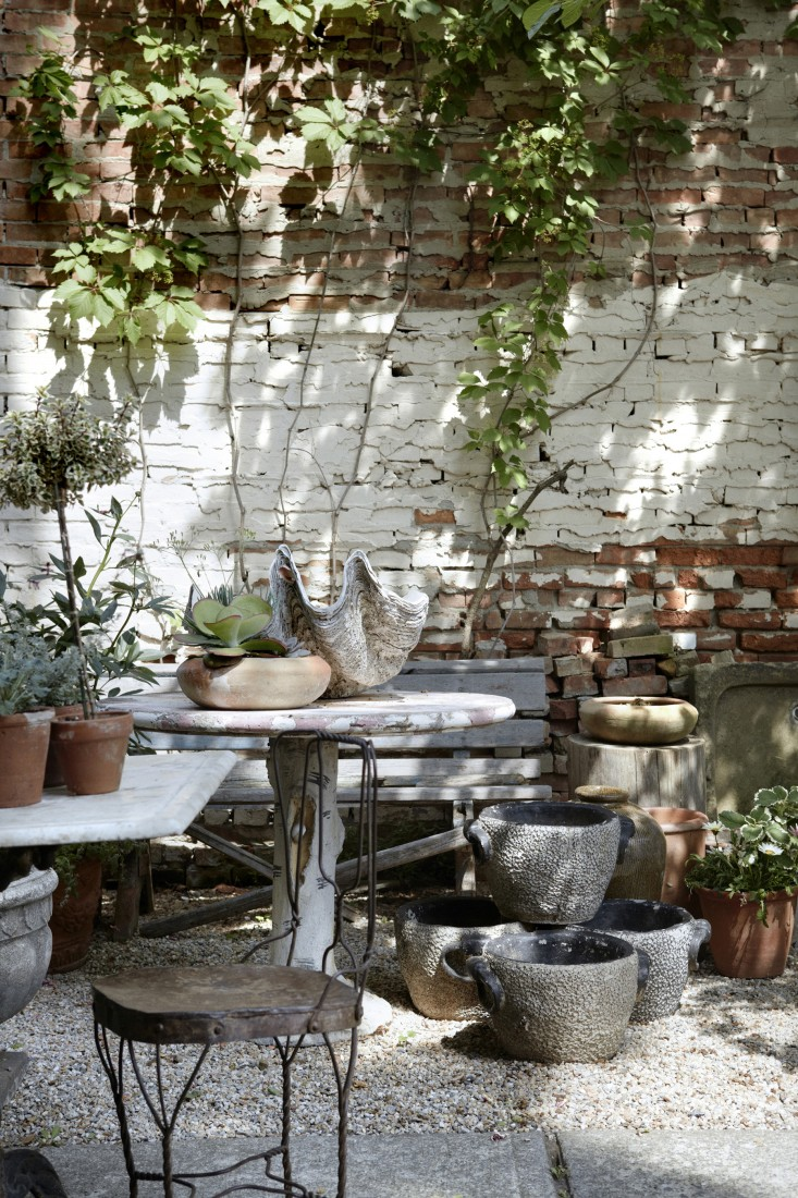 A rustic #FrenchCourtyard with vintage patio furniture and planters, brick wall, and climbing vines