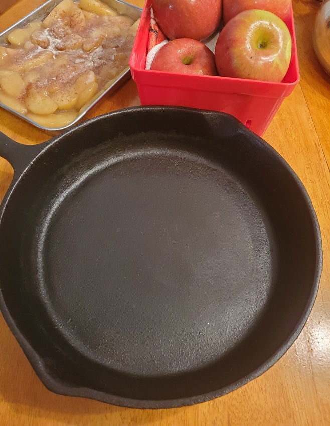 cast iron skillet and apples with a baking sheet full of country baked apples are in this photo