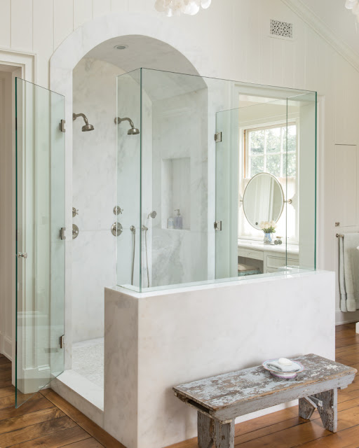 Elegant bathroom with glass walled shower and arch detail by Giannetti Home
