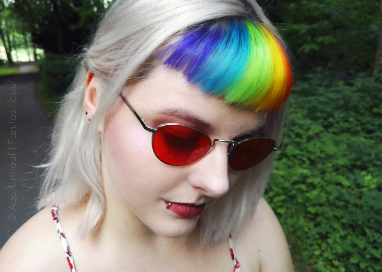 the face of a blonde white woman wearing red sunglasses with vertically rainbow colored bangs, standing in a forest