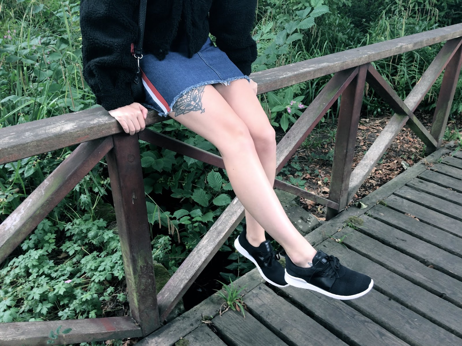 Denim skirt and black trainer combo, girl sitting on side of a bridge