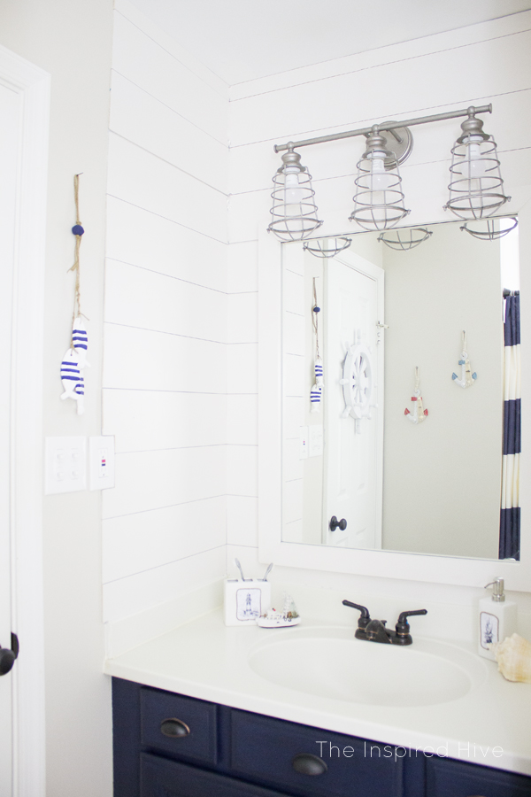Get the nautical look in your bathroom with a galvanized light, painted cabinets, and nautical accessories.