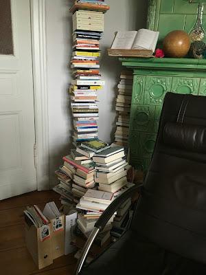 Sessel am Kachelofen, davor stapelweise Bücher