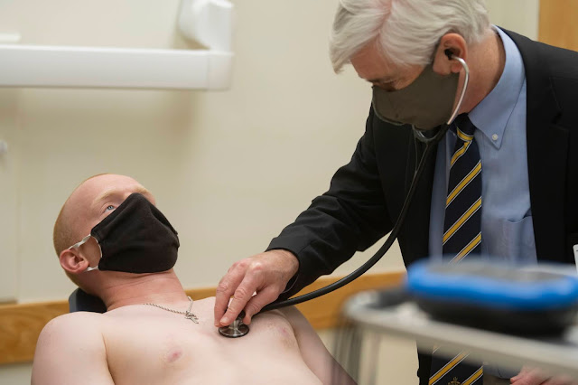 A doctor examines a man prior to an electrocardiogram.