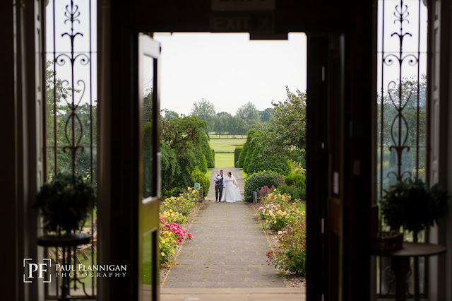 wedding couple in grounds of backworth hall through the doors
