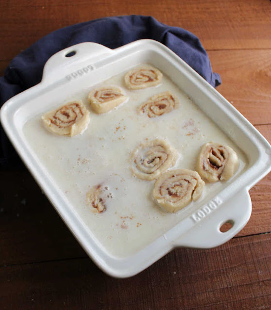 raw butter rolls in hot milk mixture, some completely submerged, ready to bake