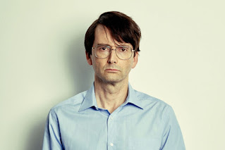 David Tennant looking serious with lank hair, big round glasses and a blue shirt with a large collar