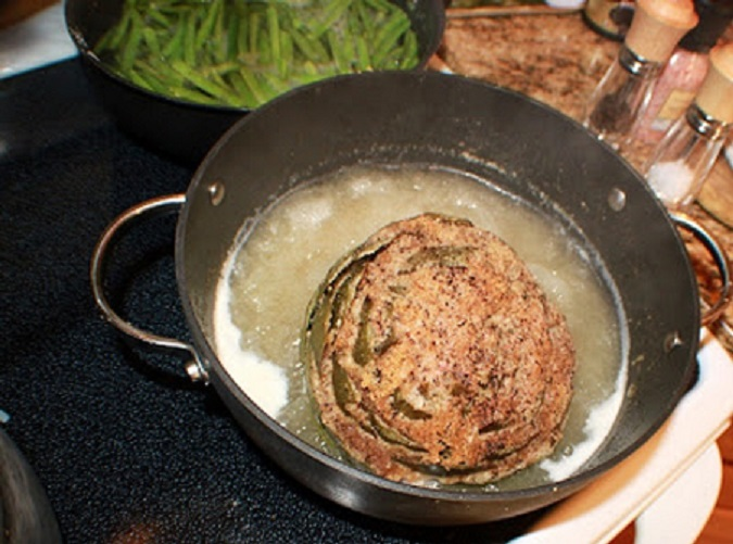 this is a stuffed artichokes in a saucepan cooking in chicken broth