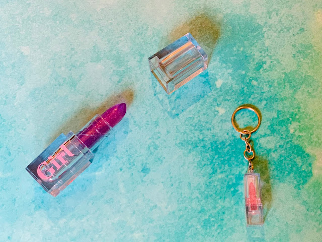 A lipstick in a clear tube and a miniature version on a key ring