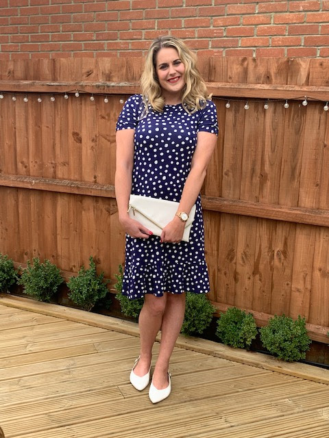 Lady posing in blue and white polka dot dress with white accessories