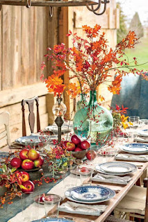An outside Thanksgiving table set on a blonde wood table with blue and whit settings and a colorful leaf centerpiece.