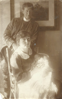 Mother seated with young baby in arms, father standing behind