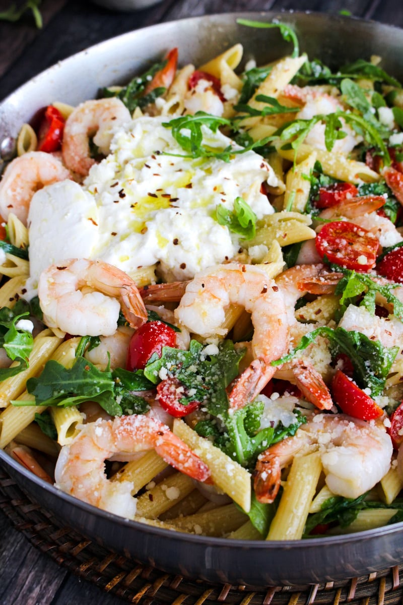Side view closeup of Shrimp, Arugula, and Burrata Pasta in a stainless steel skillet.