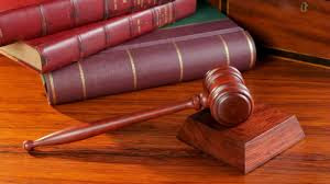 A foto mostra livros e o martelo do juiz para determinar o veredito da detença dos julgamentos.