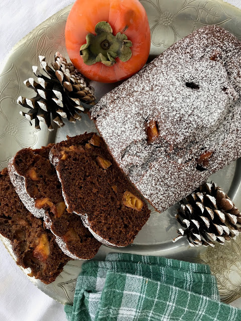 A baked loaf of persimmon gingerbread with three pieces sliced showing the center.