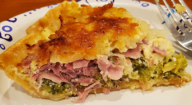this is a sliced of savory baked pie that has a layer of broccoli, potatoes, and capicola hot ham with melted 4 cheeses