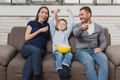 Parents and a young boy watching TV