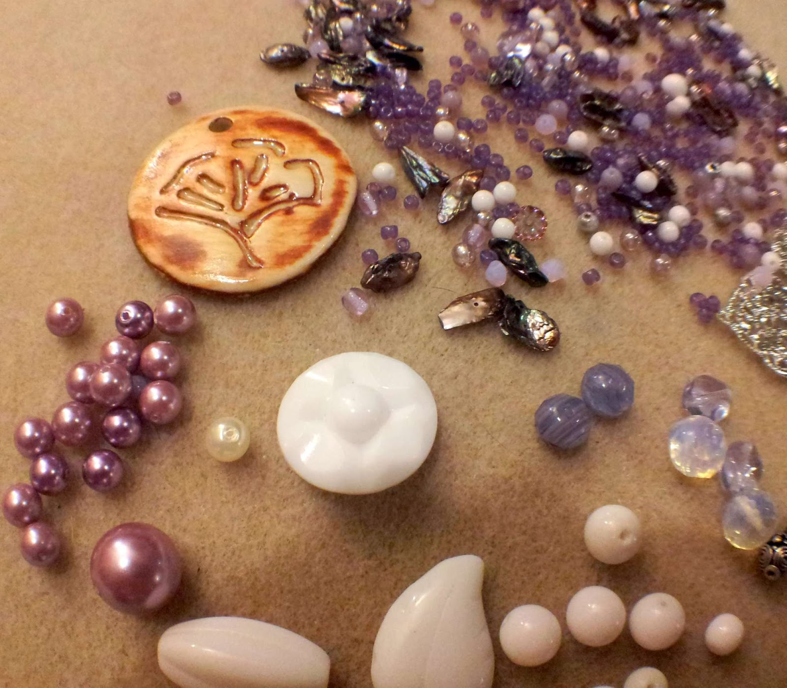 Into the forest elements: purple, white, and silver beads in various mediums (glass, ceramic, metal, glass pearls, mother of pearl) and teeny-tiny seed beads, along with a tree ceramic focal by Marla James :: All Pretty Things