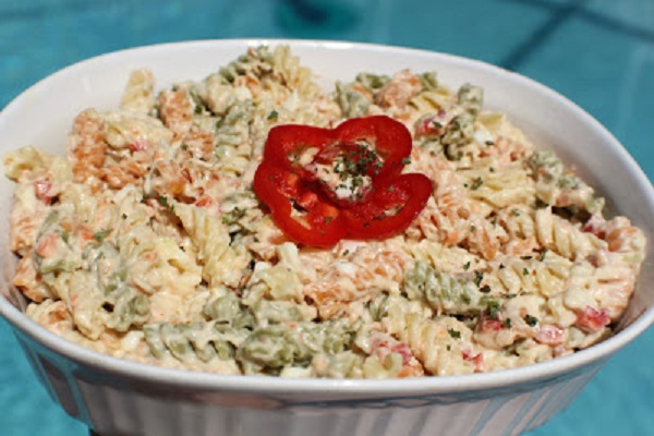 This is tri colored spiral pasta made into a macaroni salad with tuna in a glass white casserole dish