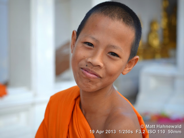 © Matt Hahnewald, Facing the World, people, portrait, street portrait, Thailand, Buddhism, Buddhist monk, orange robe, shaved head, saffron robe, Theravada Buddhism, bhikkhu, temple boy, temple, wat, Phetchaburi, religion, culture, face, eye contact