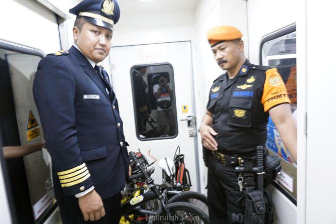 Petugas Kereta Api yang mengecek sepeda