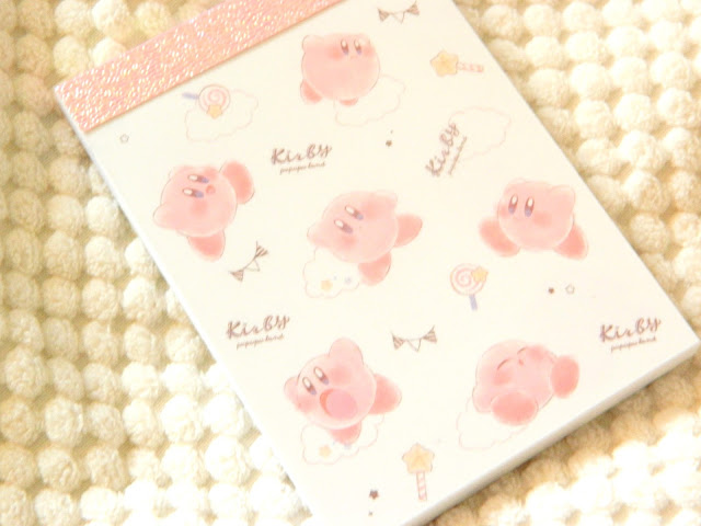 A photo showing the cover of a mini Kirby notepad, covered in cute kirby's, lollipops and wands