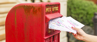 A red post box with a hand putting a handful of letter into the post box