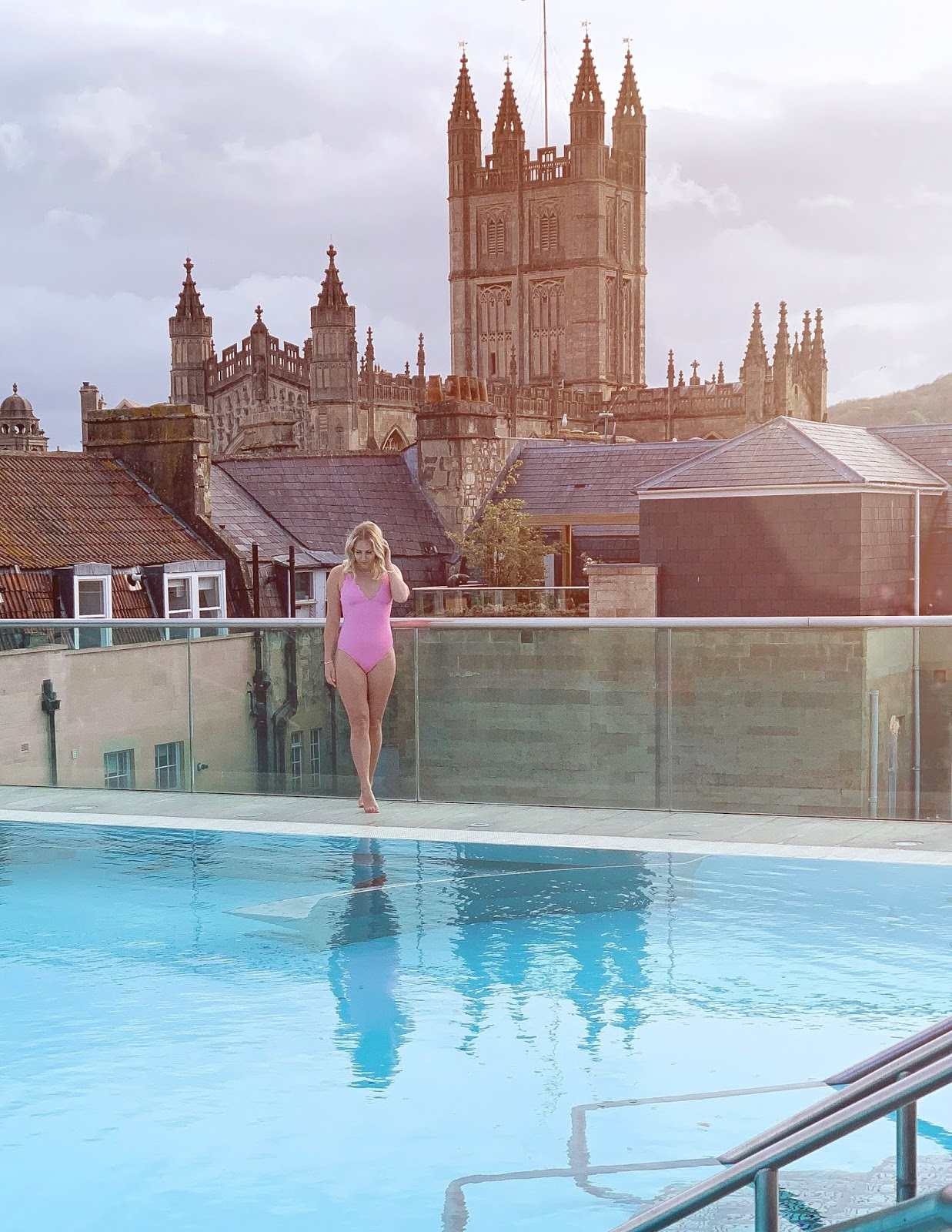 Rachel Emily on the Rooftop Pool at Thermae Bath Spa with the Cathedral in the background and sunrise