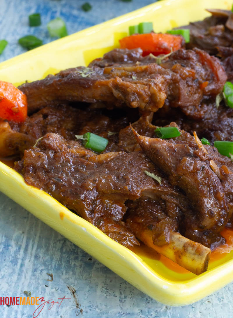 Slices of cooked lamb stew on a yellow plate
