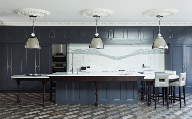 Alternative view of a kitchen in a suburban London home with blue grey cabinets, marble counter tops and backsplash, stainless appliances, silver pendant lights, carved crown moulding, ceiling medallions, parquet wood floors and leather barstools