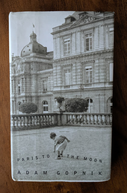 The cover shows a small boy bending over to pick up a pebble in a Parisian park.