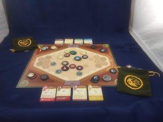 A game of War Chest in progress. The board has several tokens around it, with the draw bags nearby, several piles of tokens around it, and four cards on each side.