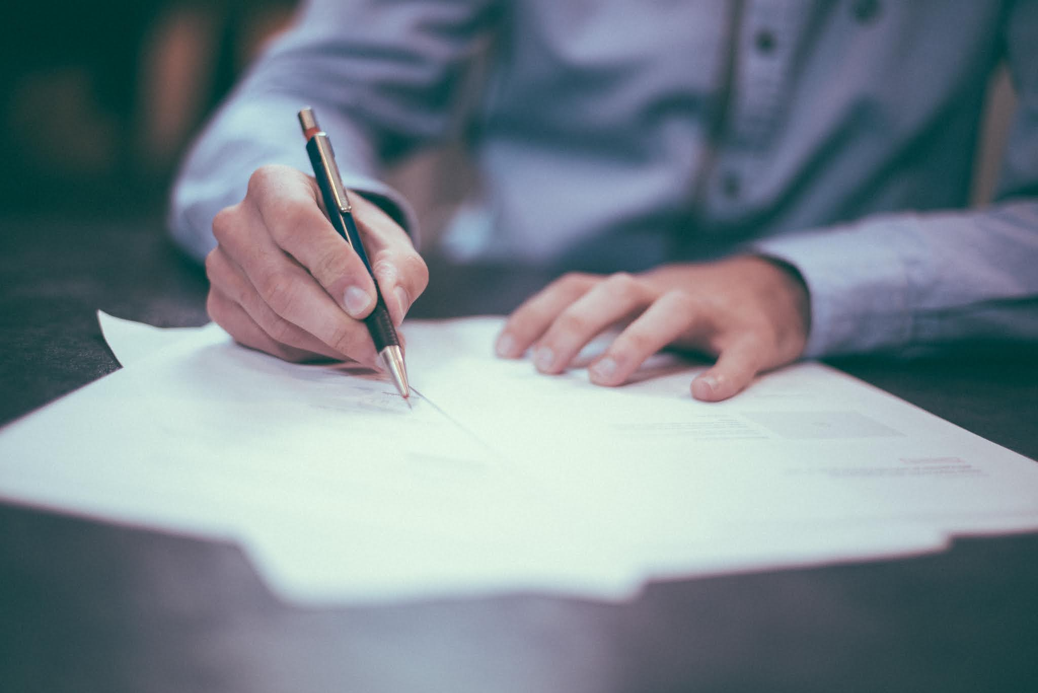 A man signing papers with a pen writing a will