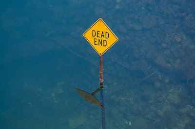 """Photo of a yellow diamond """"Dead End"""" road sign flooded to mid-post and reflected in the water underneath."""