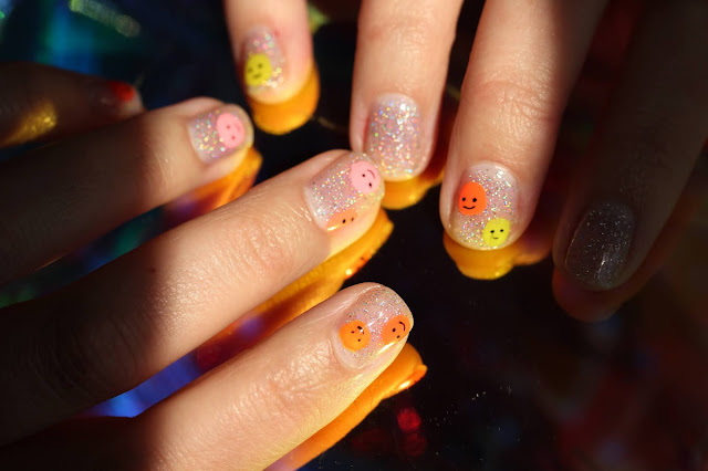Easy smiley face nail art featuring a sparkly background