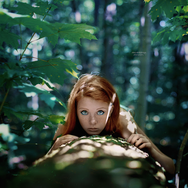 Model with red hair and big eyes laying down on the tree in the forest