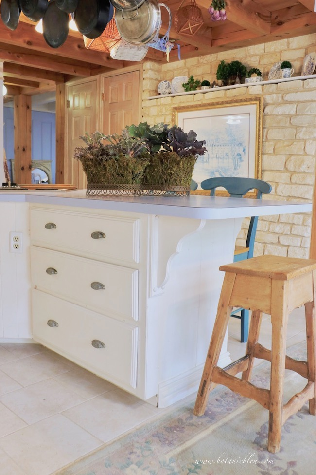 fall french country kitchen with stone wall decorated with ornamental kale