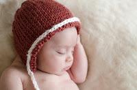 Bebé recién nacido con gorrita. Accesorios para bebé. Fotografía realizada en el estudio Positive de Roldán por Leticia Martiñena, fotógrafa de bebés recien nacidos y niños en Positive Roldán. New Born