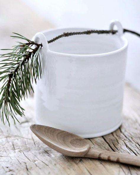 white ceramic mug with pine sprig draped on it