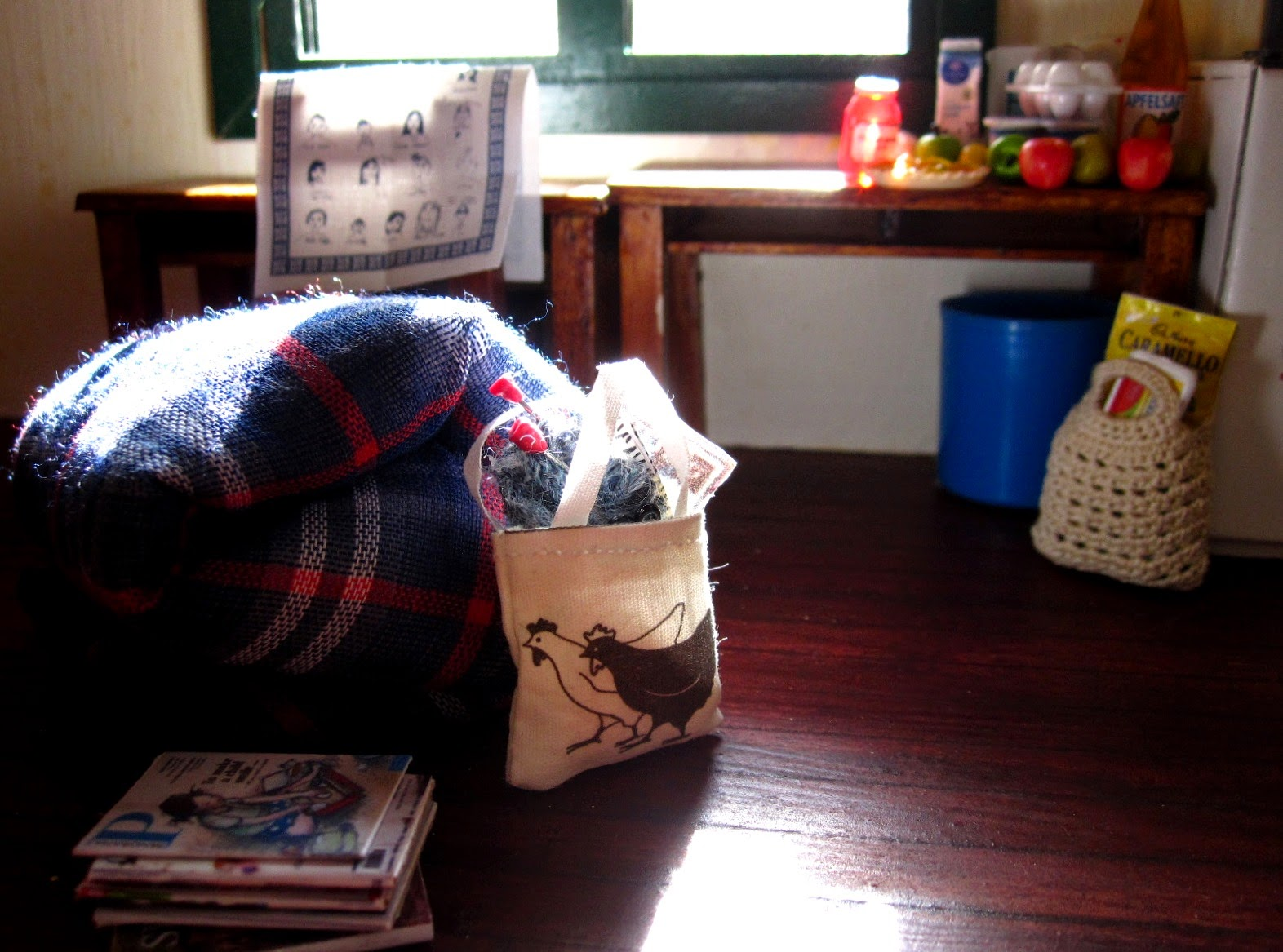 Inside of a miniature holiday house, showing a doona rolled up on the floor next to a pile of magazines and a bag of knitting. On the table behind is a selection of miniature grocery items, and a bag of groceries is on the floor underneath,