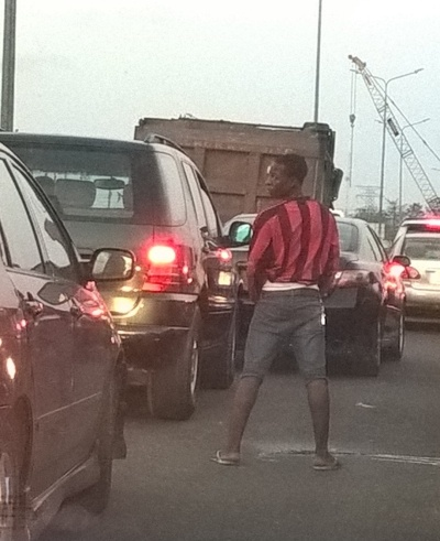 Man comes out of a bus in traffic & starts to pee on the road (photo)