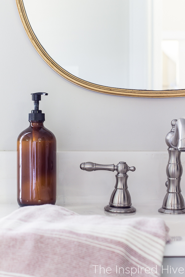 Gold mirror, nickel faucet, amber glass soap dispenser