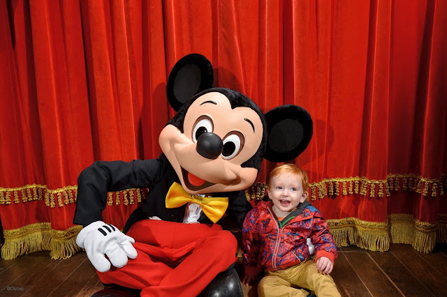 A little boy sitting with Mickey Mouse