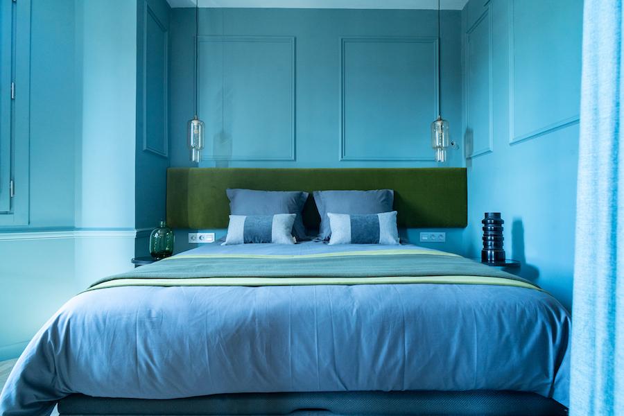 Dormitorio moderno con pared pintada de azul con molduras de escayola.