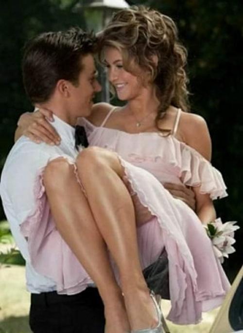 Casal feliz, ele carrega ela no colo e se olham contentes. #PraCegoVer