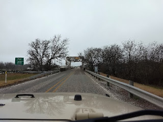 view through a Jeep windshield of road with old bridge