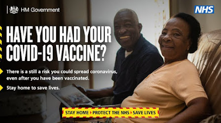 after vaccination you can still spread stay home image of two older people sitting at home grinning