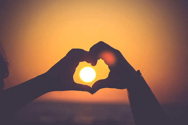 Two hands joined to make the symbol of love.
