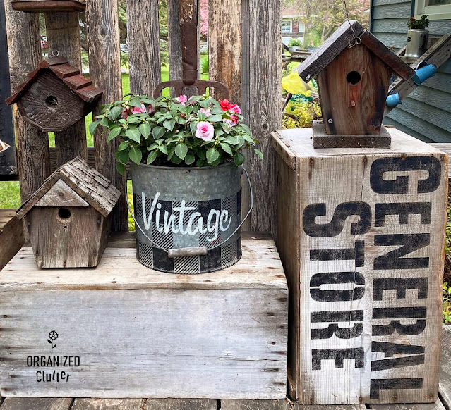 Photo of rustic birdhouses displayed with annuals and crates